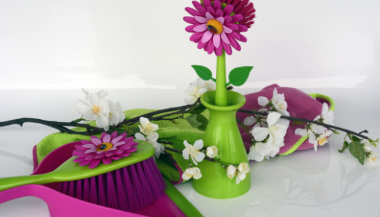 Spring cleaning challenge supplies like rags, broom, dustpan and a pretty flowered scrubbing brush in a vase.