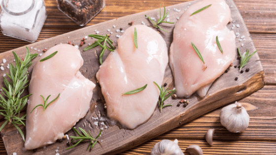 Raw chicken being prepped with seasonings as a strategy for Healthy Meal Planning