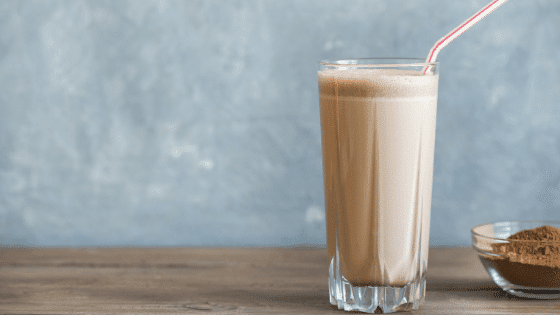 Chocolate protein shake in a glass with a straw. The easiest way to meal prep your lunch.