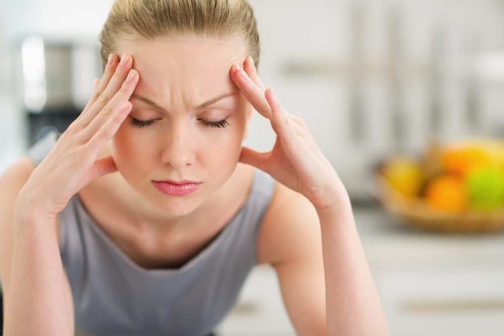 Woman totally stressed out with hands on forehead and eyes closed trying to calm down.