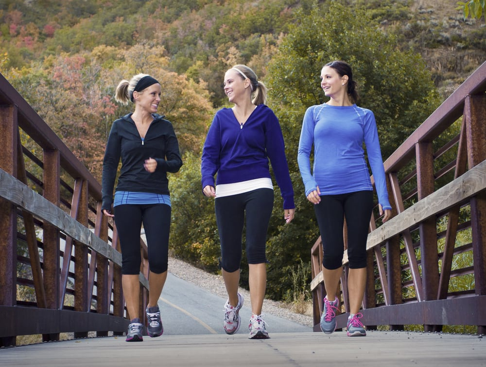 Women walking together for exercise and enjoying a quick chat as they go across a bridge.