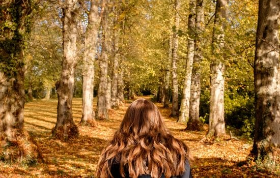Woman getting benefits of walking in the woods in the Fall. with beautiful fall leaves in her path.