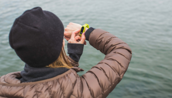 Woman in jacket standing by water looking at her yellow Garmin Vivofit fitness band.