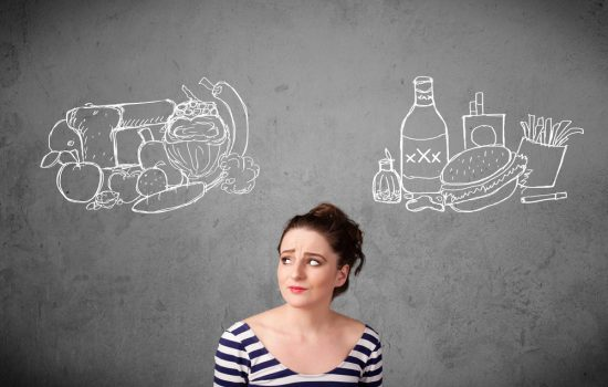 Woman thinking about Stress Eating and decinging between junk food or healthy food on displayed on the chalkboard behind her.