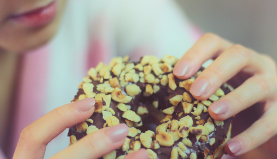 Woman eating a chocolate donut with nuts. Is this one of the signs of emotional eating? Read on to see.