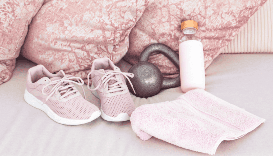 Workout shoes, kettle bell, water bottle, and workout towel sitting on a bed with pastel pink pillows.